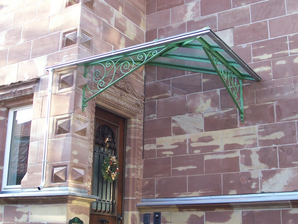 Vordach-aus-Glas--grüne-Konstruktion