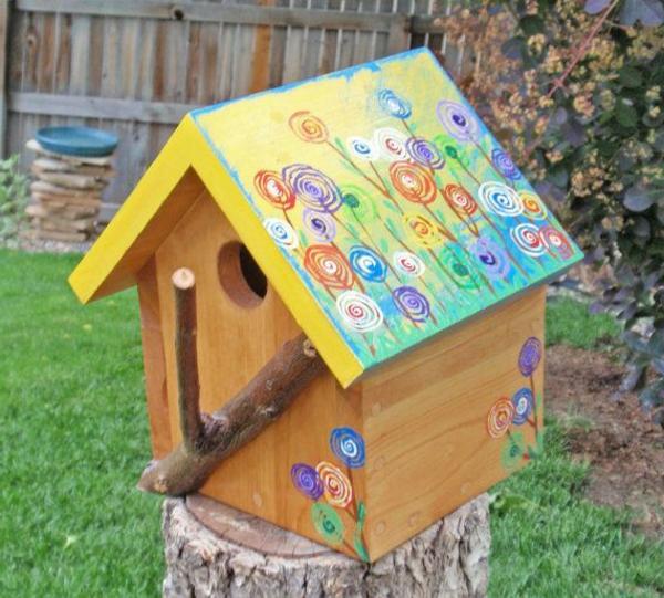 bemalte-Vogel-Futterhäuser-aus-Holz-im-Garten