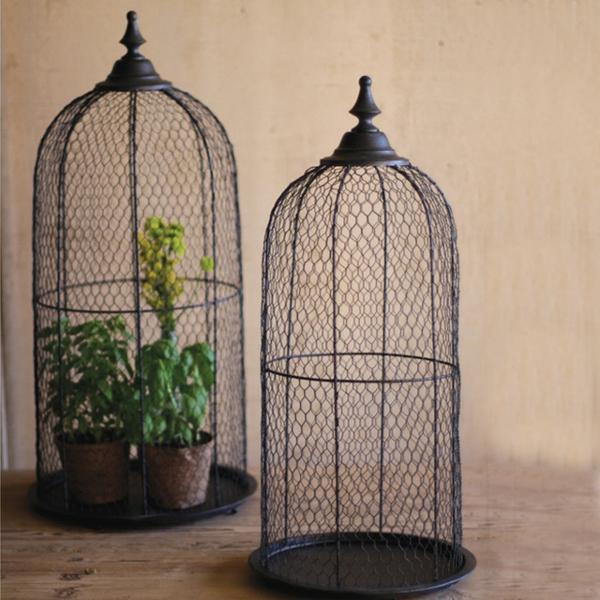 zwei vogelkäfige - der eine mit grünen pflanzen drin