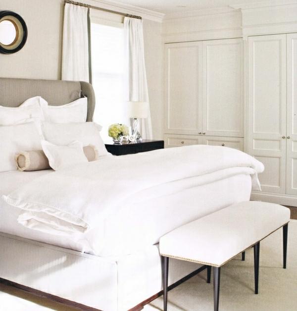 Weißes schlafzimmer mit einem bett mit vielen kissen darauf