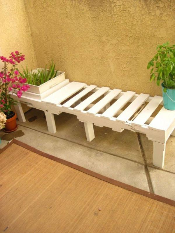 weiße-garten   bank - mit einer zyklamenfarbigen topfpflanze daneben