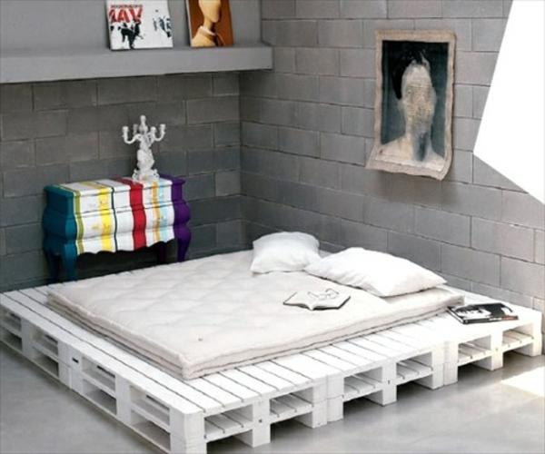 weißes-bett-aus-paletten - im zimmer mit grauen ziegelwänden