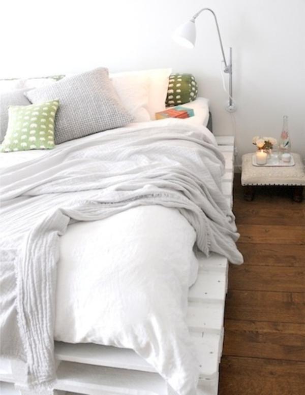 weißes-elegantes-bett-aus-paletten - eine weiße lampe daneben
