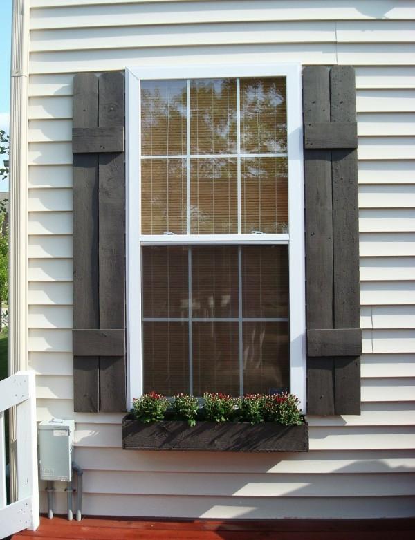 Fensterlaeden-aus-Holz-in-dunkler-Farbe