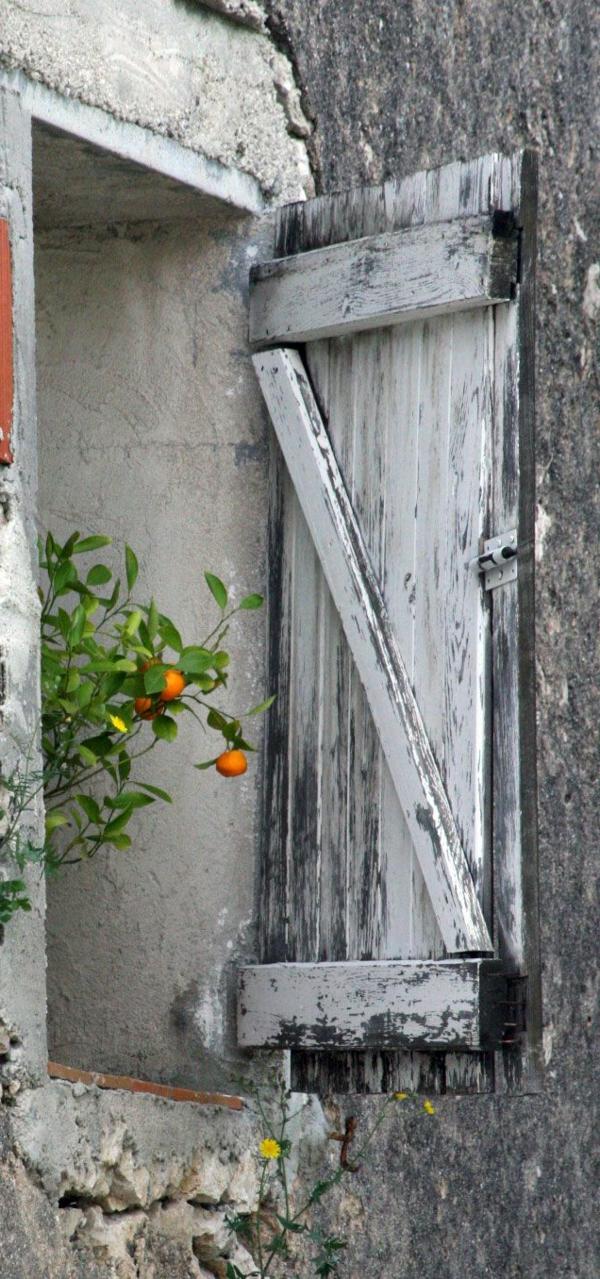 Fensterlaeden-aus-Holz-in-grauer-Farbe