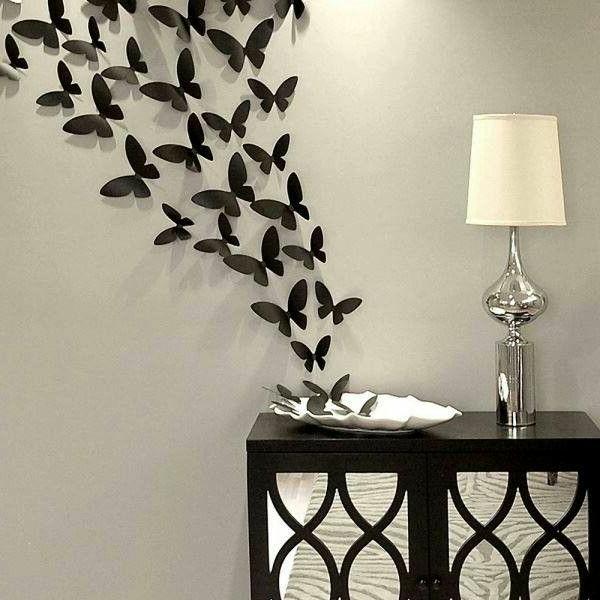 Weißes Dekokissen mit zahlreichen Schmetterlingen in schwarzer Farbe