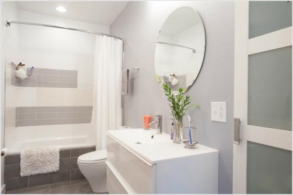 wandfarbe-hellgrau-und-runder-spiegel-im-bad