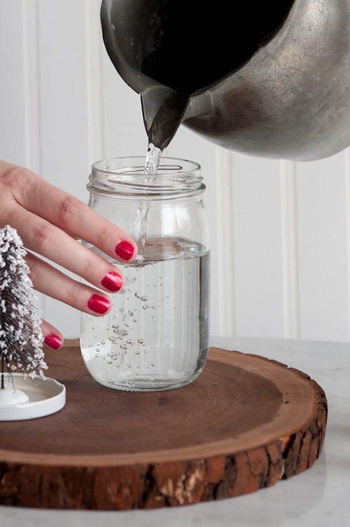 Schneekugel selber machen mit Anleitung, destilliertes Wasser geben in einfaches Einmachglas