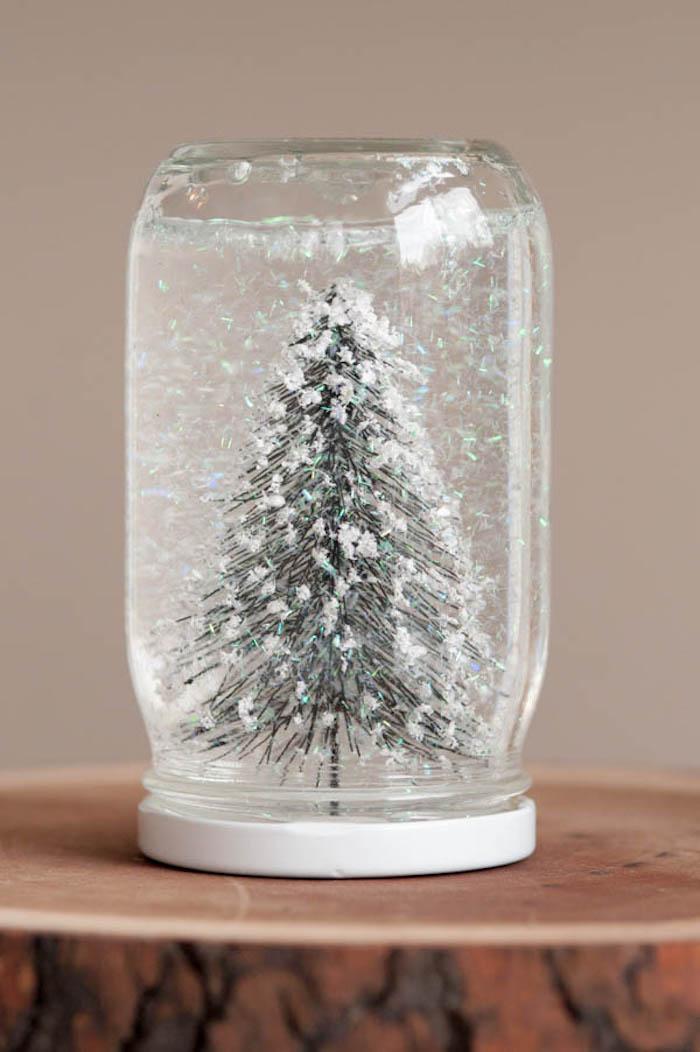 Selbstgemachte Schneekugel, Tannenbaum Figur und künstlicher Schnee in Einmachglas