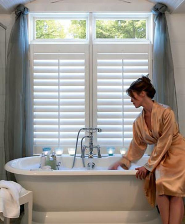 eine-frau-im-badezimmer-mit-rollos-für-badfentser