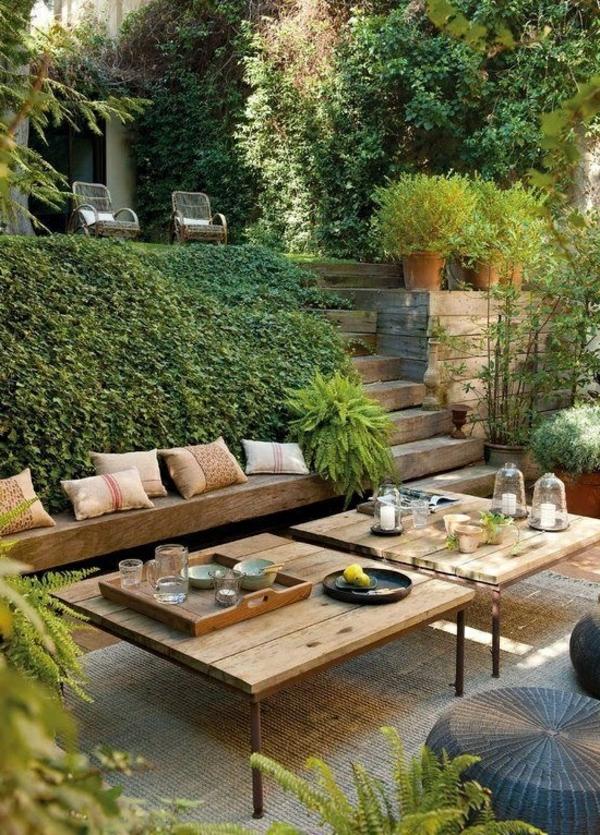 gartenbank-mit-tisch-umgeben-von-büschen- interessant und kreativ gestaltet - sehr schön