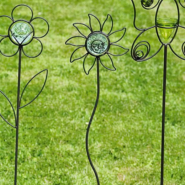 gartendeko-aus-metall-schöne-interessante-künstliche-blumen auf dem grünen gras