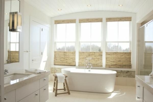 großes-weißes-badezimmer-mit-rollos-für-badfentser