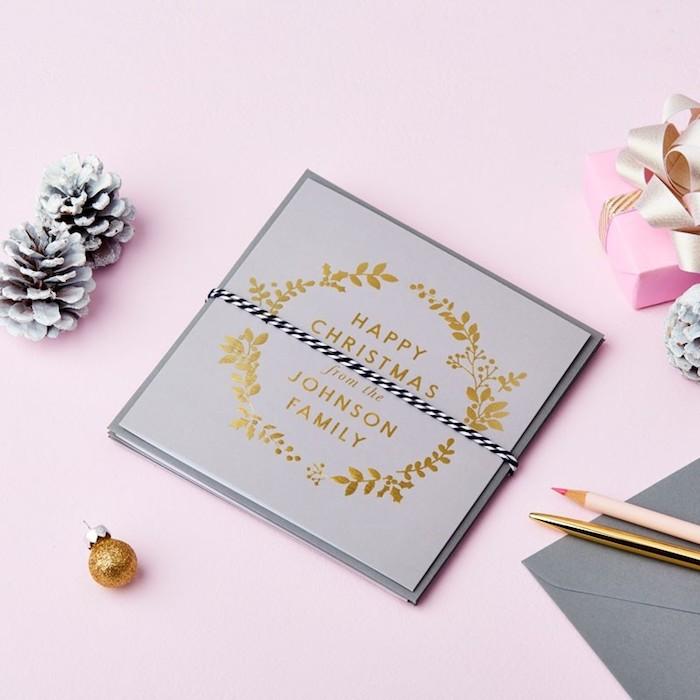 Simples Design für Weihnachtskarten, goldene Aufschrift und Verzierungen auf grauem Grund