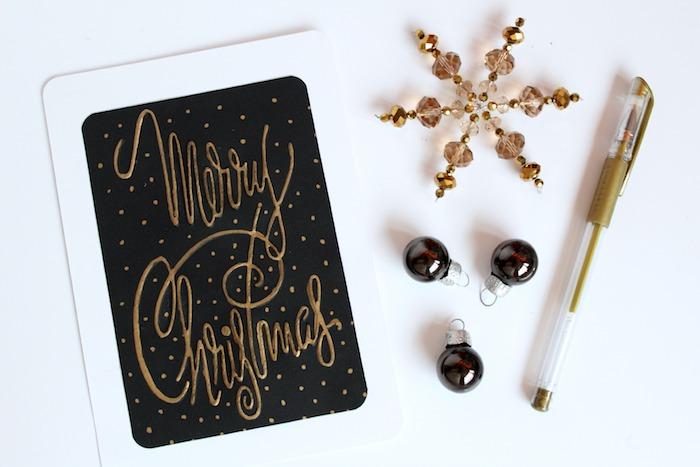 Weihnachtskarten selber machen, mit goldenem Stift auf schwarzen Grund schreiben