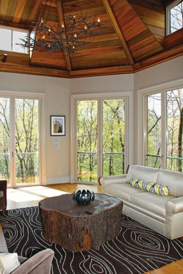 luxuriöses-wohnzimmer-mit-gläsernen-wänden-und-einem-coolen-baumstamm-tisch