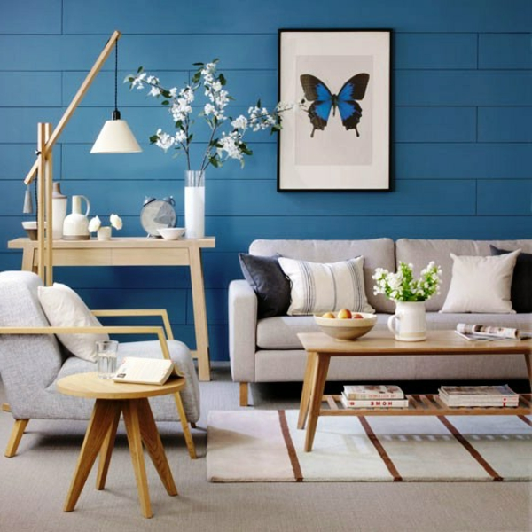 coole wohnzimmer farben:schmetterling bild an der blauen wand im wohnzimmer