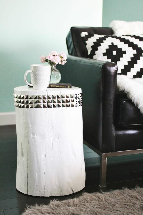 weißer-baumstamm-tisch-neben-einem-schwarzen-sofa