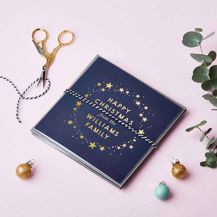 Simples Design für Weihnachtskarten, goldene Aufschrift und kleine Sterne auf dunkelblauem Grund