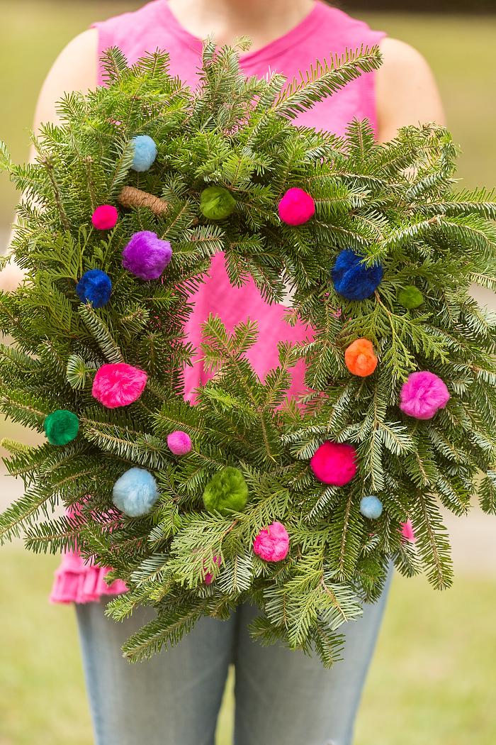 Weihnachtskranz selber machen aus echten Tannenzweigen, mit bunten Bommeln dekorieren