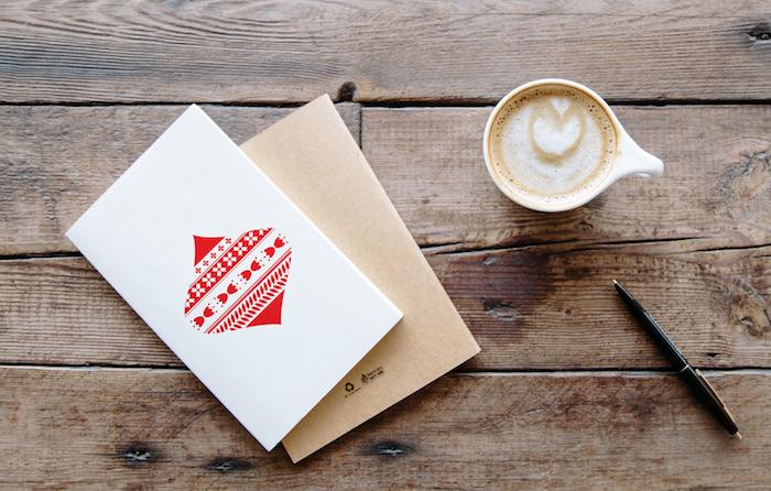 Simples Design für Weihnachtskarten, rote Christbaumkugel auf weißem Grund, Tasse Cappuccino