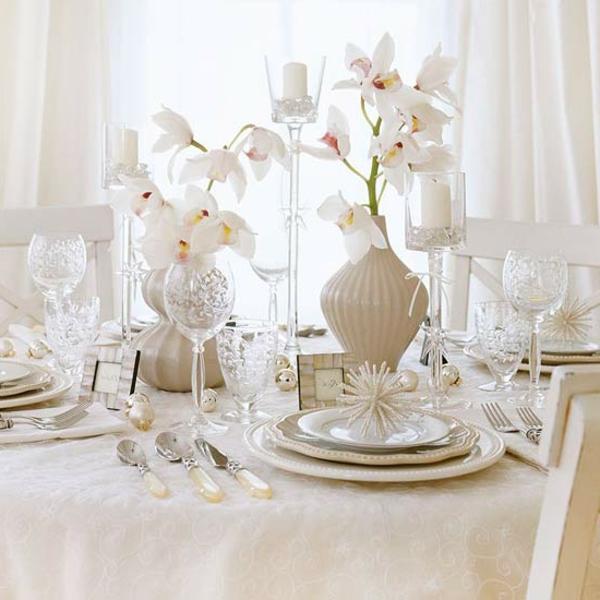 weiße weihnachtsdeko - blumen aud dem eleganten tisch