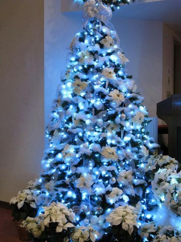 weiße weihnachtsdeko - schöner tannenbaum mit blauer beleuchtung