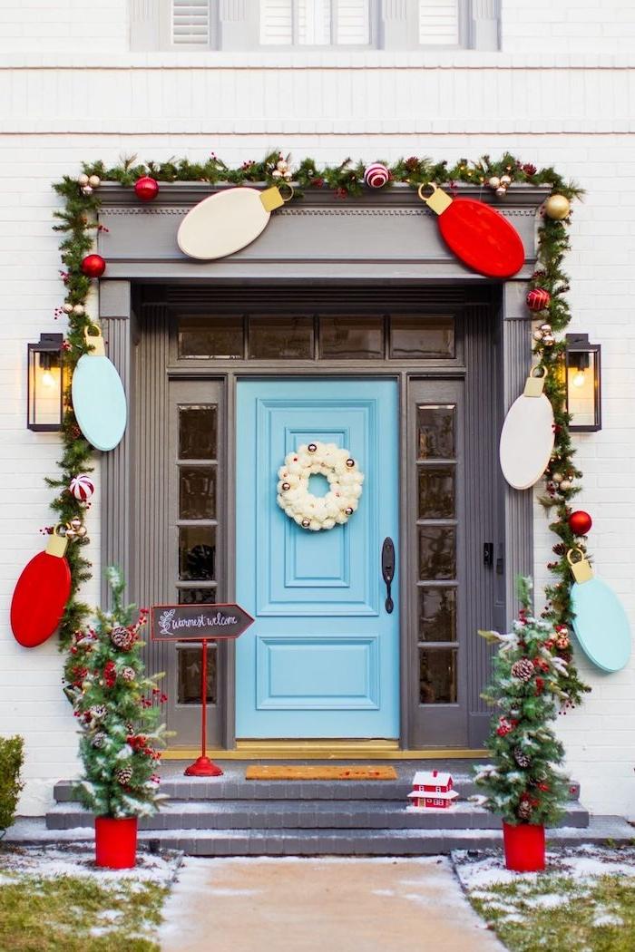 Weihnachtsdekoration für die Eingangstür, riesige bunte DIY Lichter, Tannengirlande geschmückt mit Christbaumkugeln, zwei kleine Weihnachtsbäume