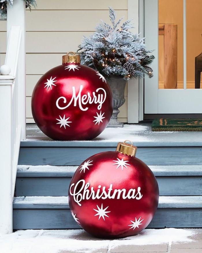 Weihnachtsdeko für den Garten, zwei riesige rote Christbaumkugeln mit weißer Aufschrift Merry Christmas und weißen Sternen