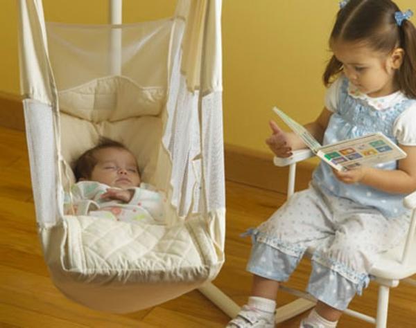 baby-hängematte-ein-mädchen-liest-ein-märchen-zu-dem-kleinen-baby