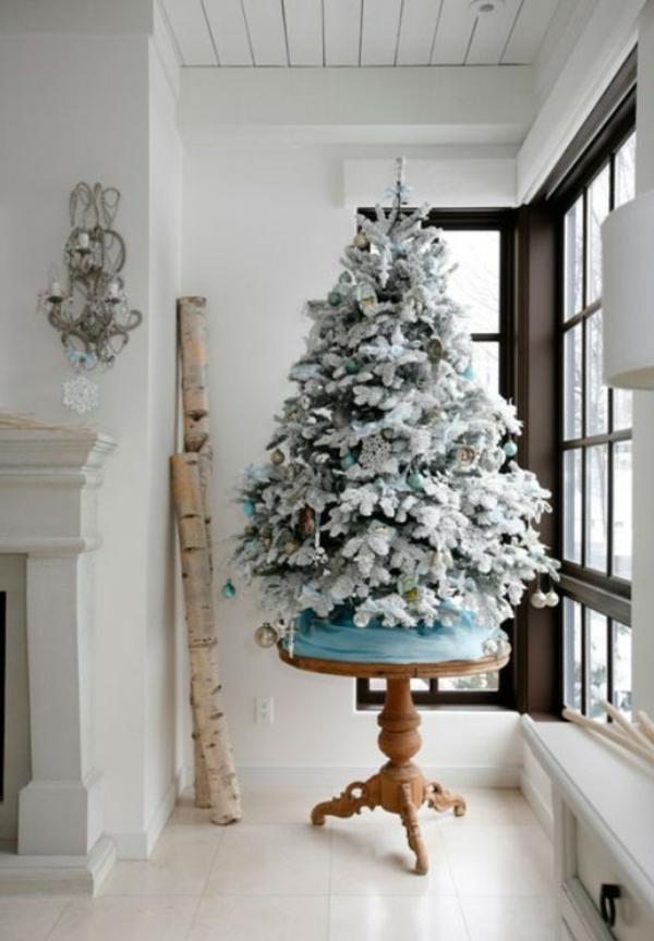 weiße weihnachtsdeko - gläserne wand und ein weihnachtsbaum daneben