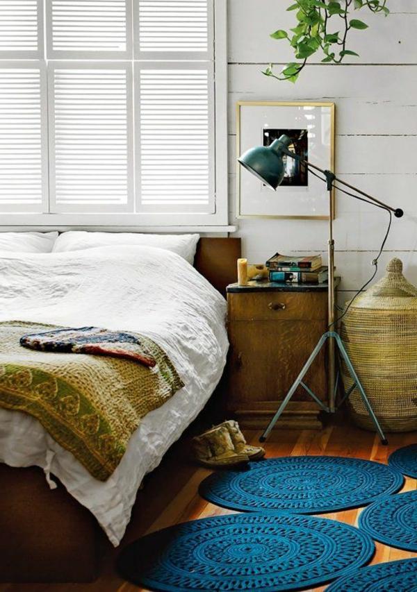 blauer-runder-teppich-neben-einem-bett-mit-weißen-bettwäschen