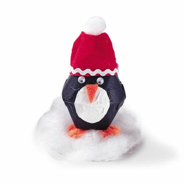 bastelideen für kindergarten - pinguin aus papier mit einer roten mütze
