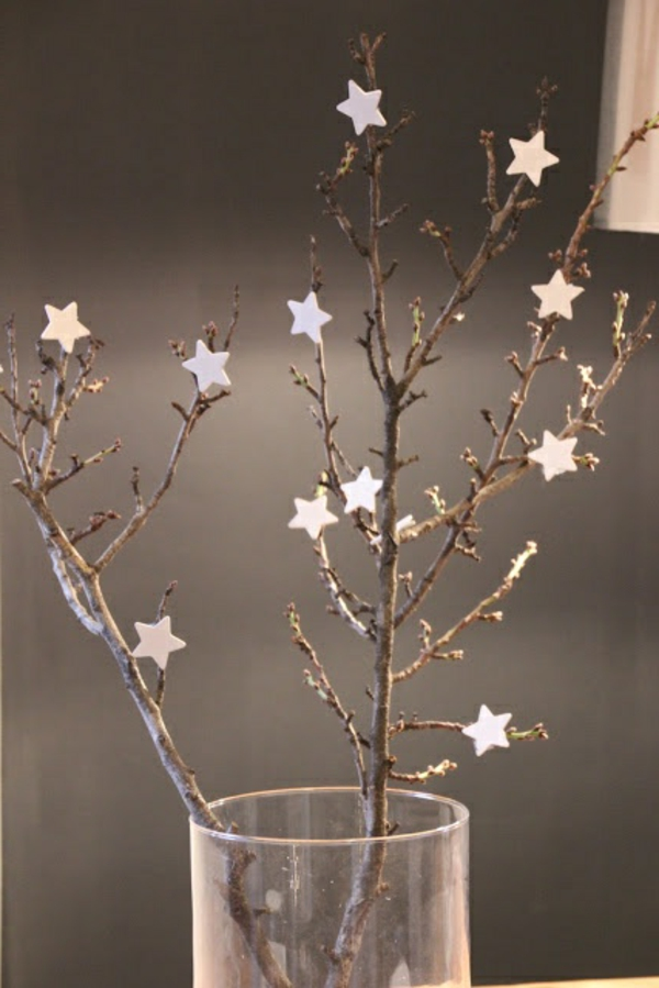 weiße weihnachtsdeko - baumzweige mit kleinen sternen darauf