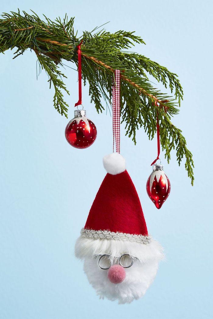 Weihnachtsdeko Ideen, echte Tannenzweige schmücken, rote Christbaumkugeln, Weihnachtsmann aus Watte mit Weihnachtsmütze