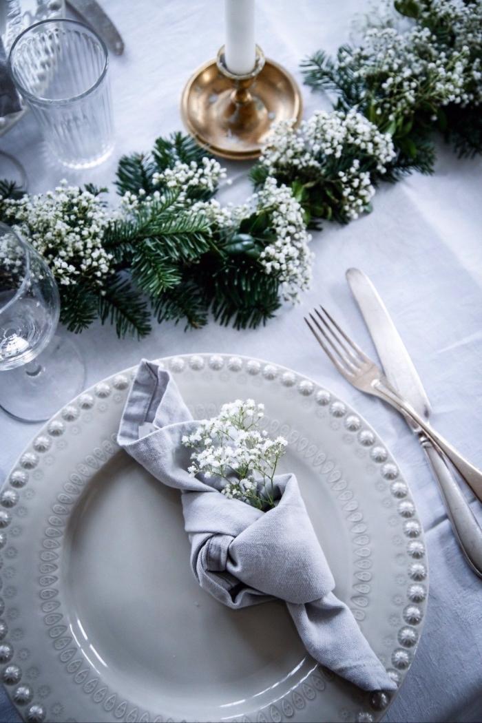 esstisch deko, graue serviette, kleine weiße blüten, immergrüne zweige, festliche weihnachtsdeko