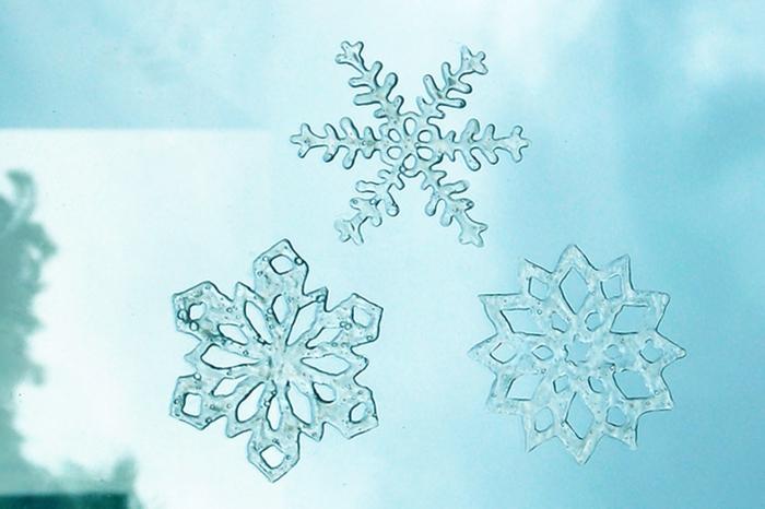 fensterdeko weihnachten basteln schneeflocken aus klebestoff transparent am fenster kleben