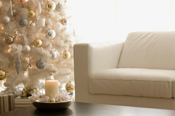 weiße weihnachtsdeko - großer tannenbaum und schickes sofa in weißer farbe