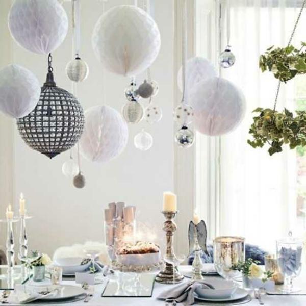 weiße weihnachtsdeko - hängende weiße kugeln über dem tisch