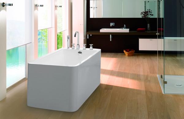 schöne badewanne in weißer farbe - neben großen fenstern