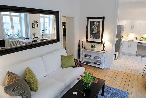 wohnzimmer mit einem spiegel über dem weißen sofa