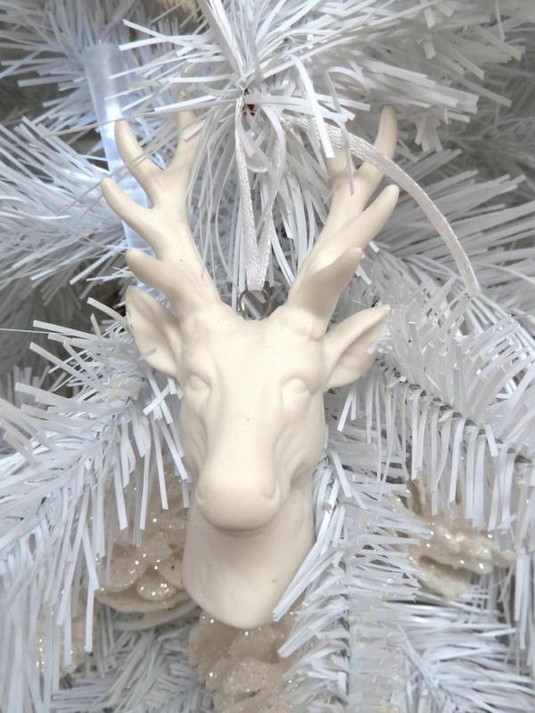 weiße weihnachtsdeko - weißer tannenbaum mit einem damhirschkopf darauf