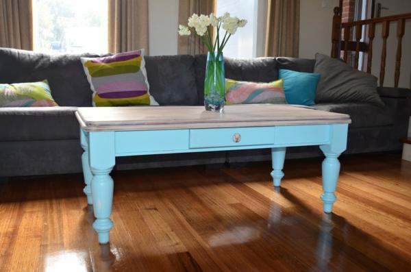 retro-couchtisch-blaue-farbe - neben einem grauen sofa