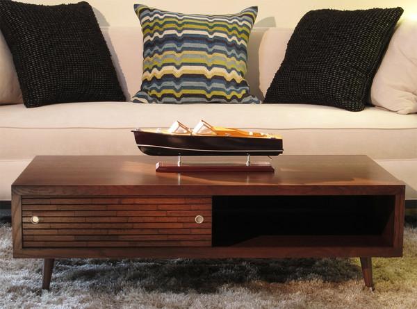 retro-couchtisch-neben-einem-schönen-sofa mit drei dekorierenden kissen