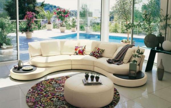 runder-teppich-unter-einem-weißen-kleinen-nesttisch-im-wohnzimmer-mit-gläsernen-wänden