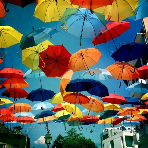 straßendeko-mit-ganz-vielen-regenschirmen-in-grellen-farben