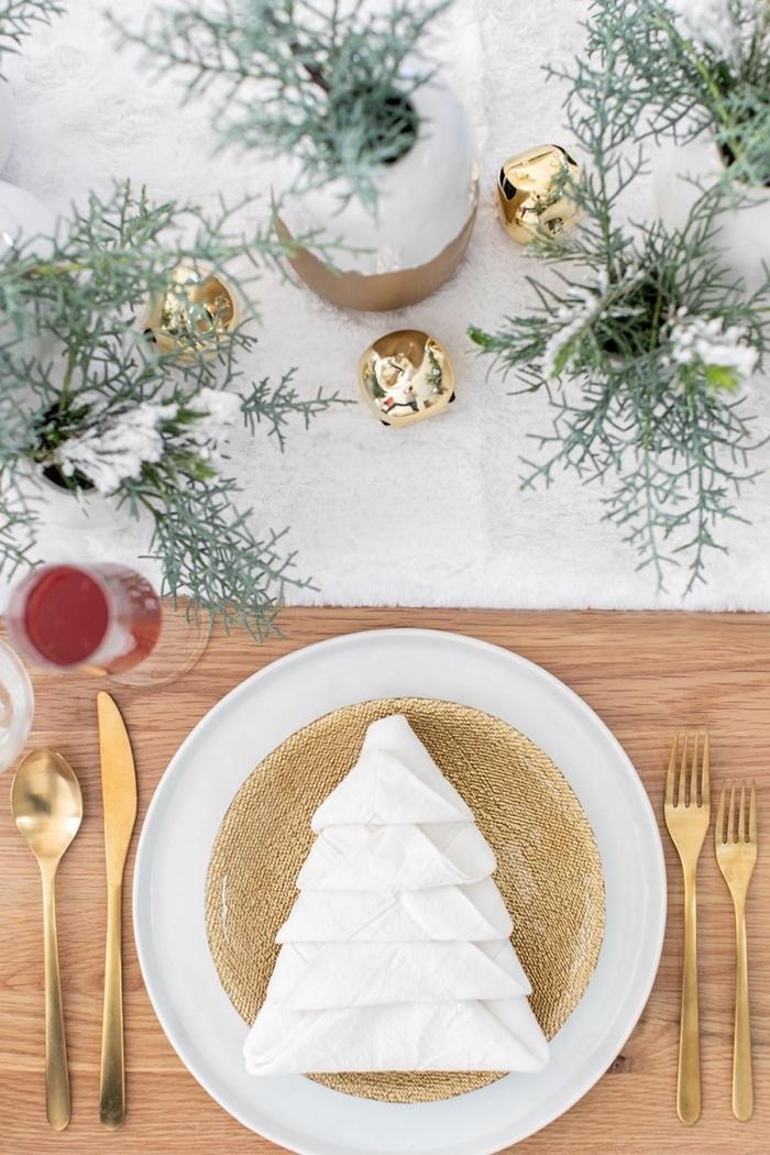 tischdeko zu weihnachten in weiß und gold, große goldene glöckchen, serviette falten