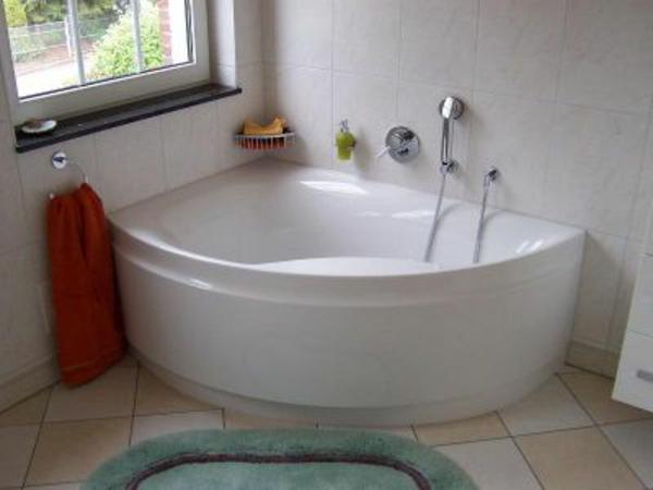 weiße-eckwanne-neben-einem-fenster - einfach ausgestattetes badezimmer
