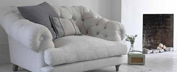 weißes-design-vom-sessel-aus-samt-mit-zwei-dekokissen-darauf