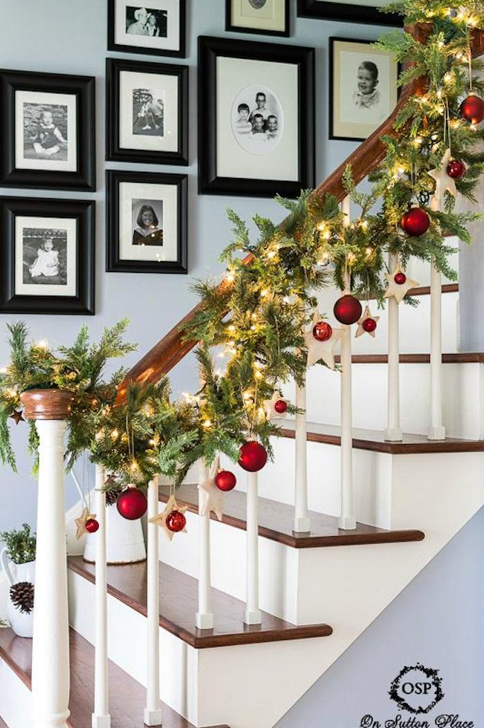 Tannengirlande mit roten Christbaumkugeln, Holzsternen und Lichtern, für Weihnachten zu Hause dekorieren